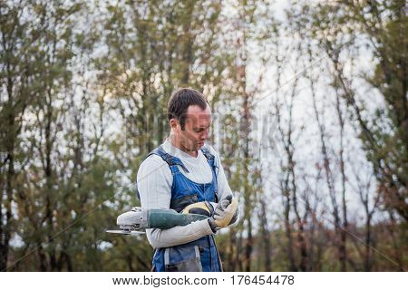 White man builder working with circular saw outdoors, portrait, telephoto shot