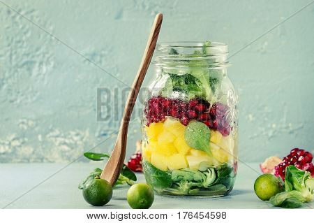 Salads in mason jar. Fruit salad with mango, pomegranate, greens. Standing with mini pineapple, limes and wooden spoon over blue texture background. Food to go. Healthy eating