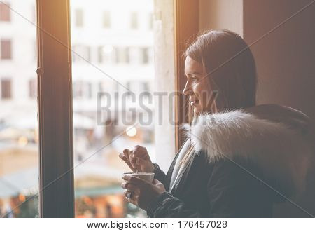 Beautiful young woman stirring her coffee with teaspoon in front of a window looking outside at the square - Gorgeous girl drinking a cappuccino while standing next to a coffee shop window