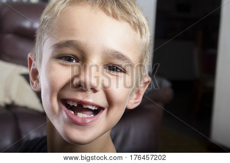 Closeup portrait of a young boy smiling with some teeth missing