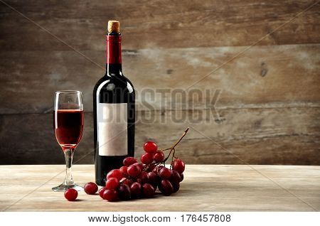 Bottle and a glass with red wine on a background of a wooden covering with grapes