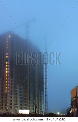 Two cranes on the construction site, unfinished houses, fog covers the upper floors, evening twilight, the lighting of the floors.