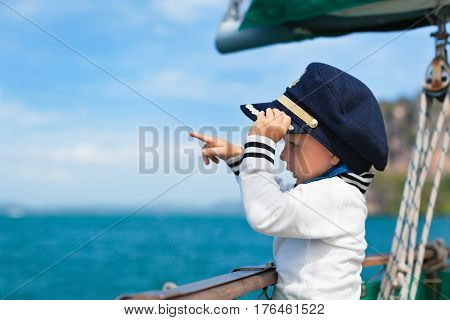 Funny little baby captain on board of sailing yacht watching offshore sea on summer cruise. Travel adventure yachting with child on family vacation. Kid clothing in sailor style nautical fashion.