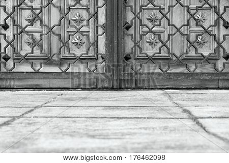 part of the closed wooden gate or door and openwork metal lattice monochrome tone