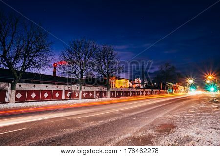 The night avenue of the city of Dobrush Belarus, the old Dobrush paper factory in the background and traces of automobile headlights on the road. Cityscape