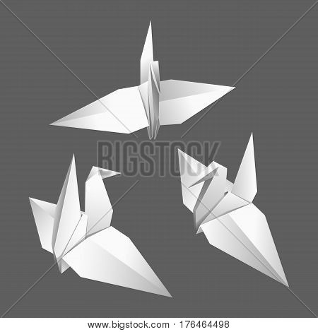 Three white paper origami birds on a gray background