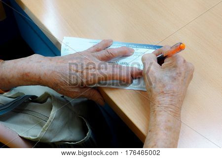 Asian grandma sign her name in deposit for open new account in Thailand bank Photo on top has copy space.