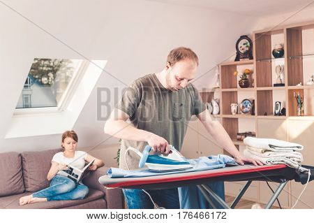 Young Woman Sitting At The Sofa Reading The Book While Her Husband Is Ironing Shirt At Home.