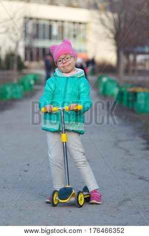 A Little Girl Is Riding A Scooter.