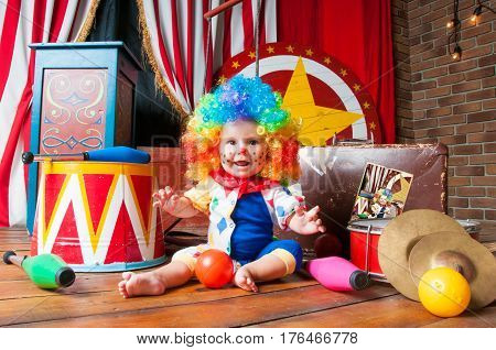 Little baby clown with red nose multi-colored wig in with balls.