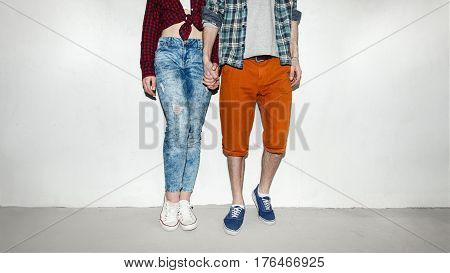beautiful couple standing by the wall staring each other