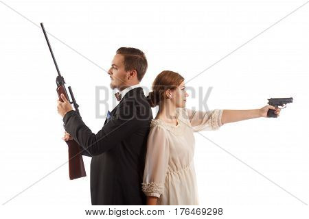 A man in a suit and a girl in a dress both holding guns