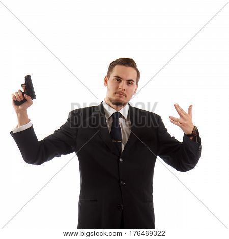 A man in a suit with a gun showing a hand gesture