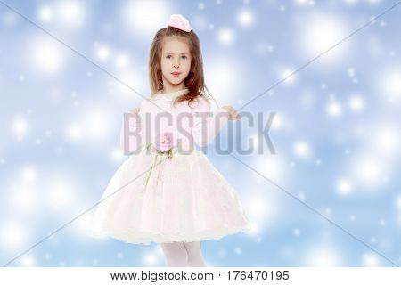 Dressy little girl long blonde hair, beautiful pink dress and a rose in her hair.She spreads her hands aside.Blue Christmas festive background with white snowflakes.