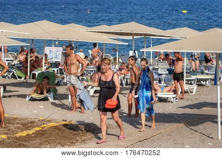 Antalya Turkey - 27 august 2014: A large concentration of vacationers on the beach of a Mediterranean resort a woman and a teenage girl return to the hotel.