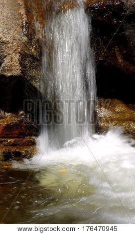 Photo of a beautiful small waterfall on a sunny afternoon