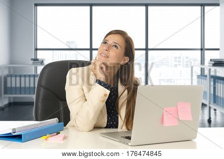 corporate portrait of young attractive woman sitting at office chair working at laptop computer desk smiling happy looking thoughtful and pensive at modern business district workplace background