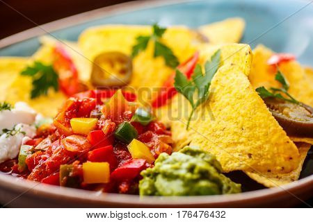 Nachos With Vegetables, Peppers And Sauce Are On The Plate.
