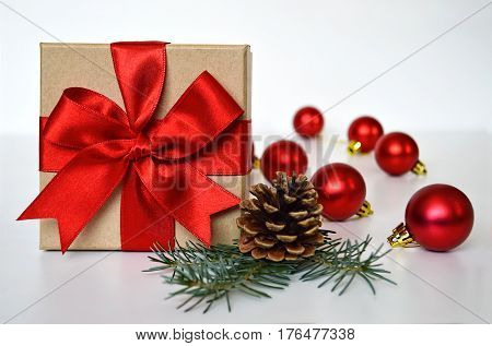 Christmas gift, red Christmas balls, pinecone and spruce branch
