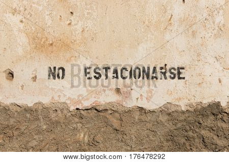 No parking sign in spanish on wall