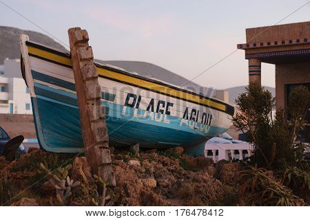 A boat a the entrance to the beach of Aglou in Morocco wiht the words Aglou Plage written on it.