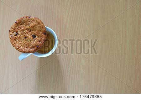 Top view of an oatmeal raisin cookie with a cup of coffee on the wooden table