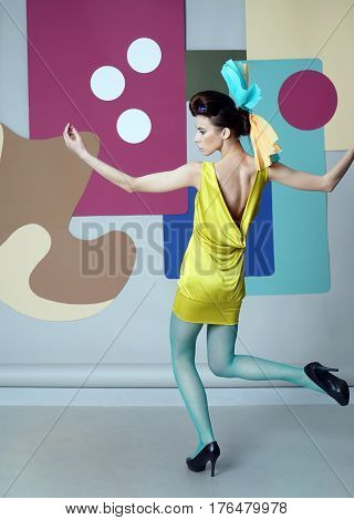 Eccentric girl dancing on the color background. Fashion story. Danish design. She dressed in short yellow dress, green tights, high heels. View from back. Backdrop: circles, Egg chair.