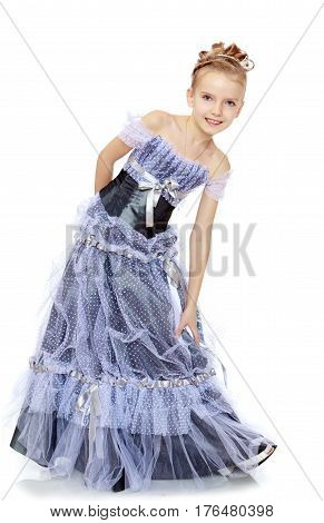 Slender little girl , with beautiful hair on her head, elegant long Princess dress. The girl twisted to the side and keeps her hand on her knee. Isolated on white background.