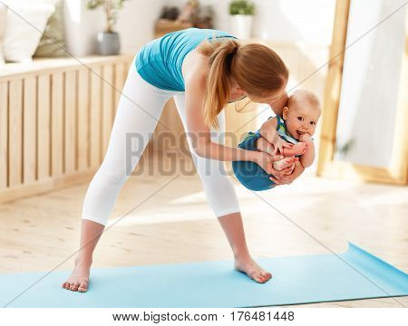 sport family. Mother is engaged in fitness with baby