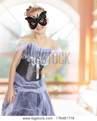 Slender little girl with beautiful hair in elegant long princess dress posing in carnival butterfly mask in a room with a large arched window.