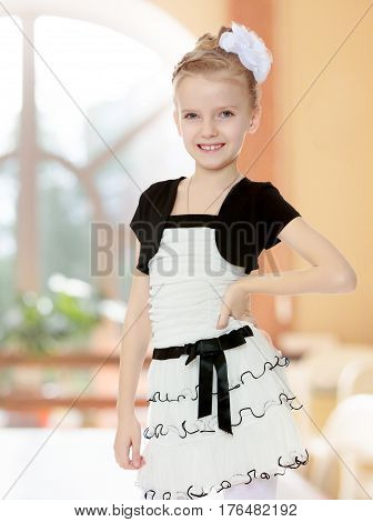 Beautiful little blonde girl dressed in a white short dress with black sleeves and a black belt.Closeup.In a room with a large semi-circular window.