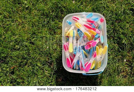 Brightly Coloured Clothes Pegs In A Bucket On Green Grass In Sunshine
