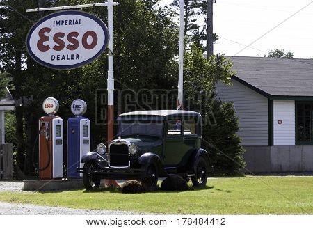 Antigonish, Nova Scotia, September 24, 2015 -- Wide view of a gorgeous green model-T Ford sits beside two old Esso gas pumps with sheep lounging beside the car on a beautiful sunny afternoon in September