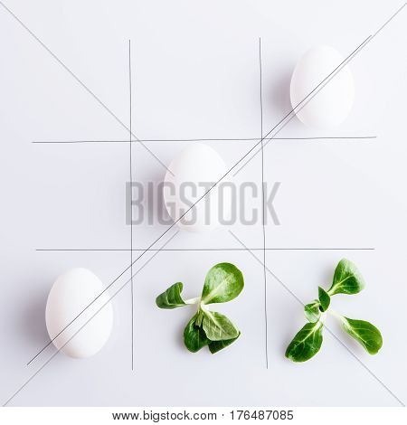 Tick-tack-toe from white eggs and corn leaves