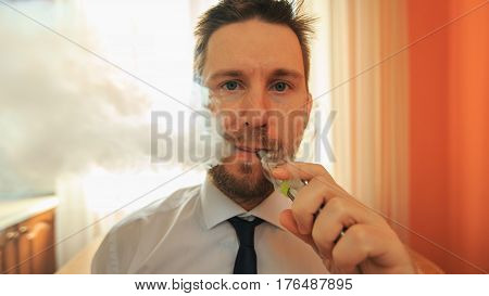 Vape. Young Funny White Businessman With Beard And Mustache Emits Puff Of Steam From The Electronic