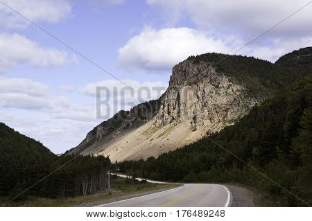 Wide view of the idyllic landscape with a scenic winding road curving past a sun bathed cliff face in Cape Breton Highlands National Park, Nova Scotia on a beautiful bright cloud filled sunny day in September.