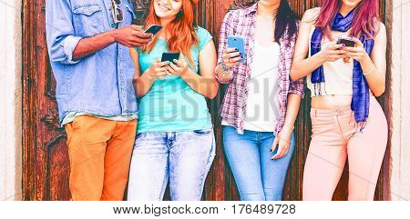 Group of teenagers texting mobile phone messages leaning against urban wall - Row of best student friends using smartphone wearing summer trendy clothing