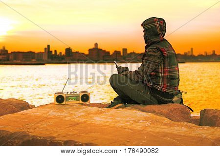 Pensive african american man silhouette sitting by the ocean looking at cityscape - Hooded guy listening music holding phone with melancholic attitude - Concept of dreams and hopes with golden filter