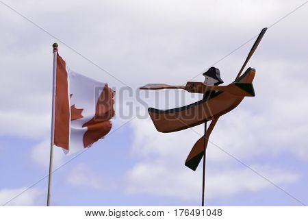A single small colorful wooden novelty boat is displayed against the blue sky with a soft focus Canadian flag in the background in Cape Breton Highlands National Park, Nova Scotia on a beautiful bright cloud filled sunny day in September.