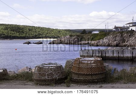 Large metal lobster traps are in the forefront beside a pier on the Gulf of St. Lawrence with homes on a rock face in the background in Cape Breton Highlands National Park, Nova Scotia on a beautiful bright cloud filled sunny day in September.