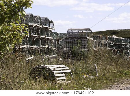 Wooden lobster traps are stacked high beside a dirt road in Cape Breton Highlands National Park, Nova Scotia, on a beautiful bright cloud filled sunny day in September.