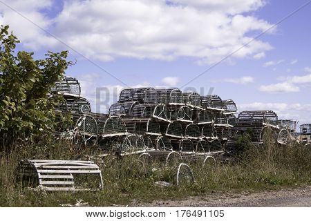 Wooden lobster traps are stacked high beside a dirt road in Cape Breton Highlands National Park, Nova Scotia on a beautiful bright cloud filled sunny day in September.