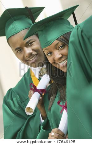 Two graduates with diplomas outside