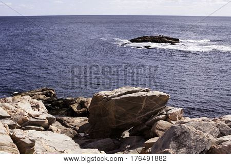 The blue seas of the Gulf of St. Lawrence with large boulders in the forefront and a single large rock outcropping with a flock of birds sunning themselves in Cape Breton Highlands National Park, Nova Scotia on a beautiful bright sunny day in September