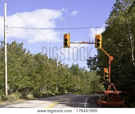 A mobile set of traffic lights is parked beside a rural highway in Cape Breton, Nova Scotia on a beautiful bright sunny day in September.