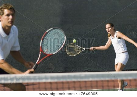 Mixed Doubles player hitting tennis ball, partner standing near net poster