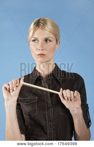 Businesswoman stretching rubber band, on blue background, portrait