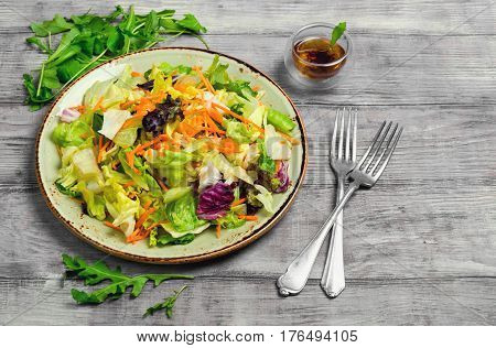 Fresh salad from lettuce leaves of different kinds of varieties cabbage carrots rucola salad. Sauce for salad from lettuce leaves forks. Light white wooden background.