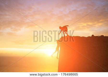 silhouette of businesswoman with dangerous problem in cliffs