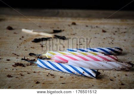 Used birthday candles and matches burned and blackened. Left scattered on a wooden chopping board with cake crumbs as remnants at the end of party celebrations.